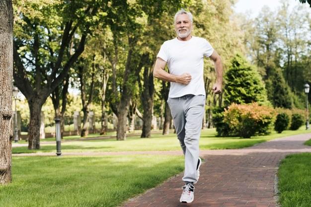 пожилой мужчина пенсионер бежит по парку